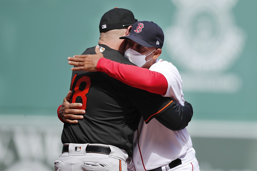 Boston Red Sox manager Alex Cora, right, hugs Baltimore Orioles manager Brandon Hyde before an opening day baseball game, Friday, April 2, 2021, in Boston. (AP Photo/Michael Dwyer)