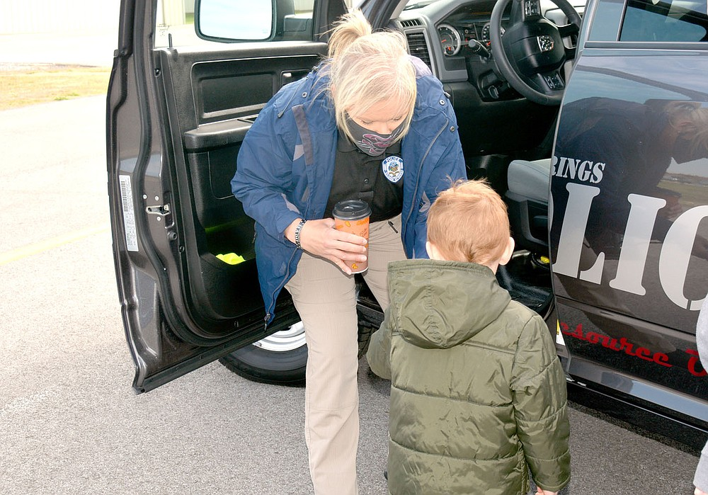 Marc Hayot/Herald-Leader Officer DeAndra Strickland hands Jacob Hughes a magnet, one of two give aways the Siloam Springs Police Department handed out to children on Kite Day.