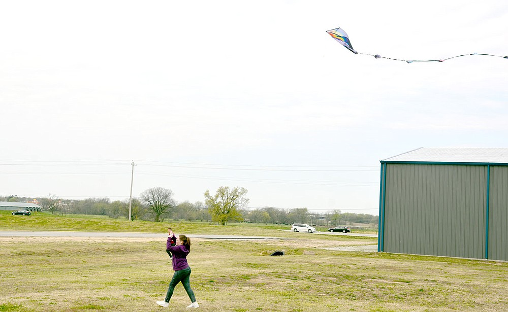 Marc Hayot/Herald-Leader Macie Davis trots down the grass so her kite will fly high. Davis is one of several people who came out to fly their kites on a windy Saturday at the airport where the city held Kite Day.