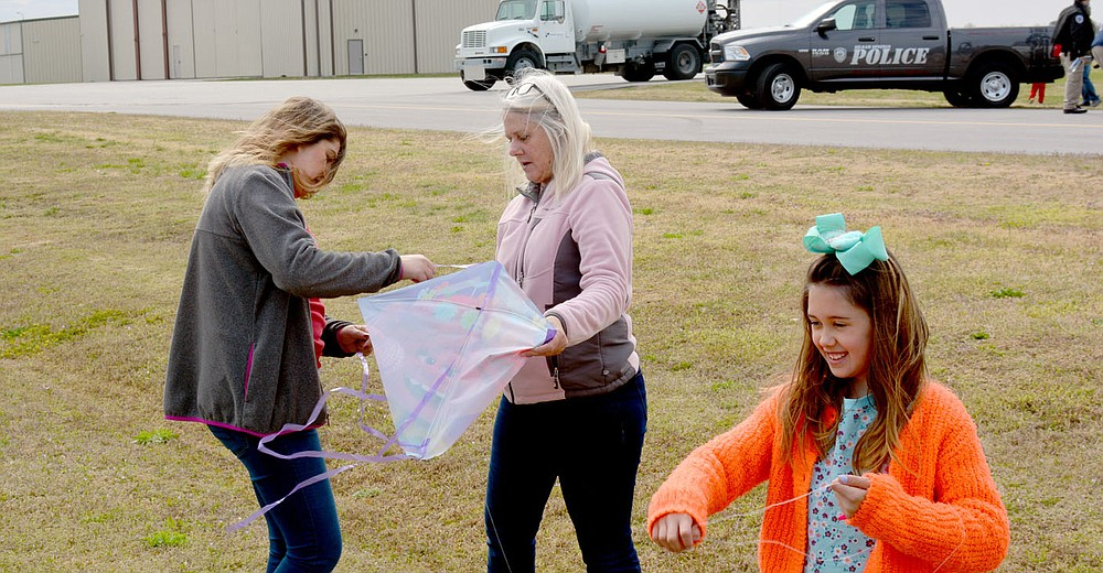 Marc Hayot/Herald-Leader Kelly Quick (left). and Julie Mitchell works fix a kite as Sophia Bedlin attempts to fly her kite during Kite Day.