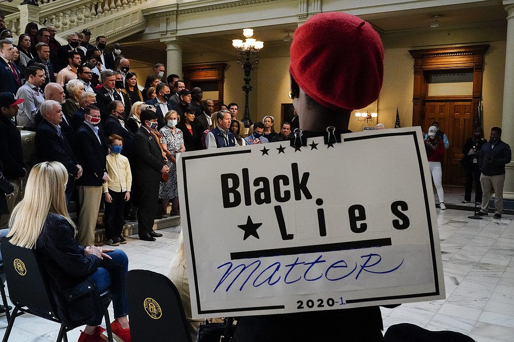 "A supporter wears a ""Black Lies Matter"" sign as Georgia Gov. Brian Kemp speaks during a news conference at the State Capitol on Saturday, April 3, 2021, in Atlanta, about Major League Baseball's decision to pull the 2021 All-Star Game from Atlanta over the league's objection to a new Georgia voting law. (AP Photo/Brynn Anderson)"