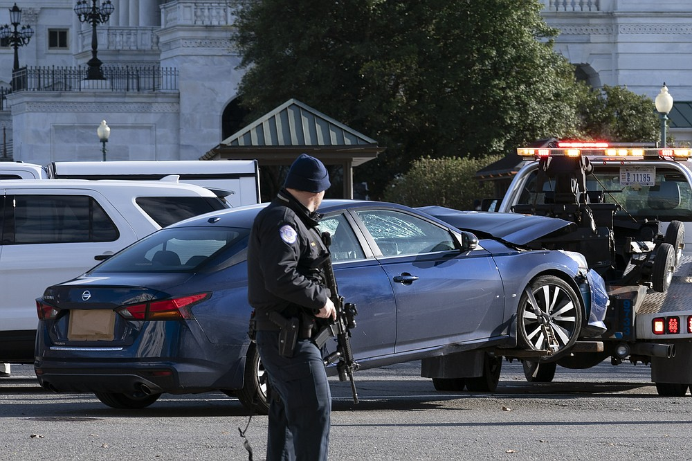 Authorities tow a car after a man rammed it into a barricade on Capitol Hill in Washington, Friday, April 2, 2021. (AP Photo/Jose Luis Magana)