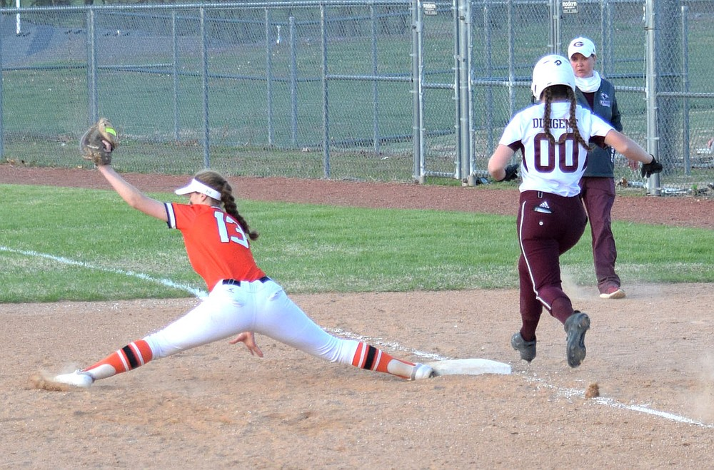 Westside Eagle Observer/MIKE ECKELS  Taylor Neustel stretches as far as she can to catch the ball during the Friday night Gravette-Gentry softball contest at Lion Softball field in Gravette. Neustel's effort paid off as the umpire call Lady Pioneer runner Madi Voyles out at first base.