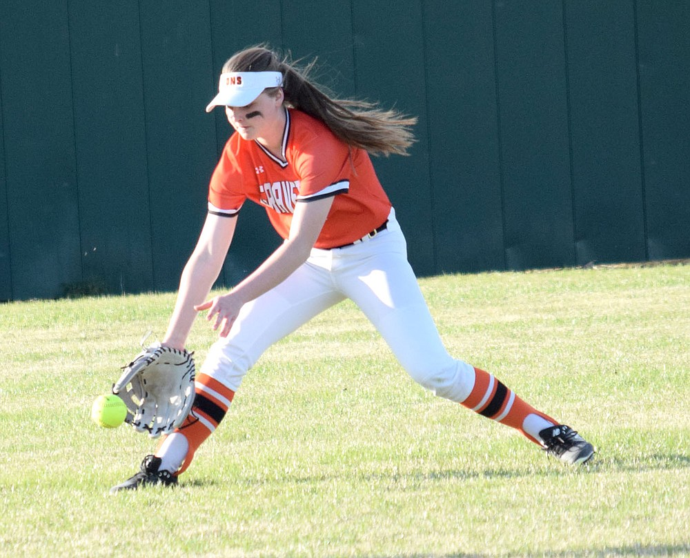 Westside Eagle Observer/MIKE ECKELS  Keeley Elsea picks up a ground ball in center field during the Gravette-Gentry softball contest in Gravette Friday night. Elsea was abel to throw to her cutoff person forcing the Lady Pioneer batter into a single base hit.