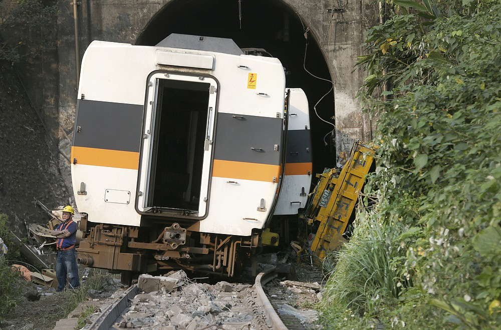 A worker stands in front of the derailed train near Taroko Gorge in Hualien, Taiwan on Saturday, April 3, 2021. The train partially derailed in eastern Taiwan on Friday after colliding with an unmanned vehicle that had rolled down a hill, killing and injuring dozens. (AP Photo/Chiang Ying-ying)