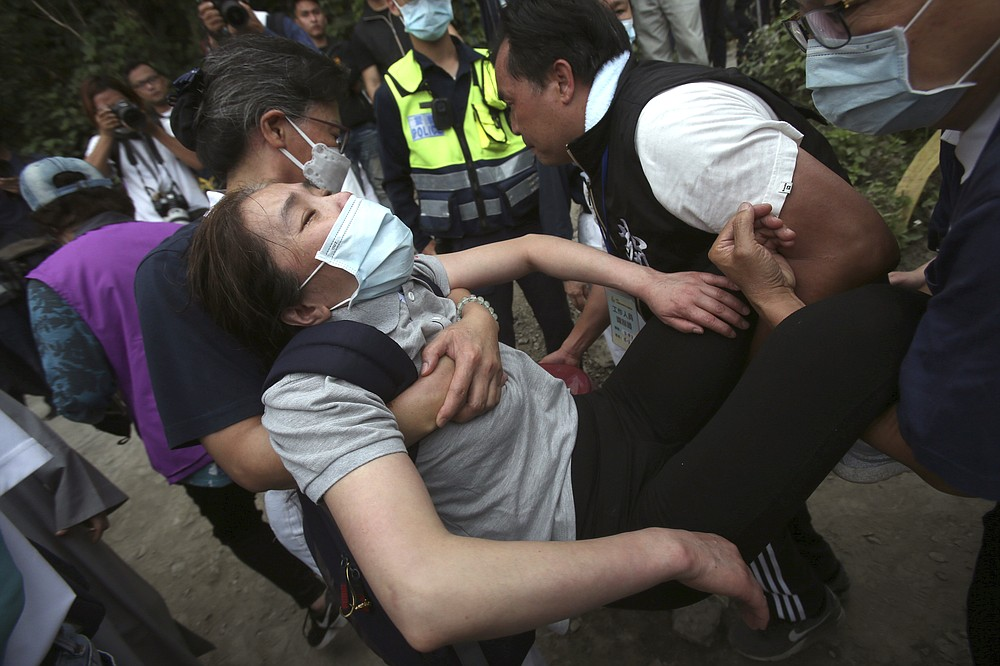 A distressed woman is carried away as families mourn for the victims in a train accident near Taroko Gorge in Hualien, Taiwan on Saturday, April 3, 2021. The train partially derailed in eastern Taiwan on Friday after colliding with an unmanned vehicle that had rolled down a hill, killing and injuring dozens. (AP Photo/Chiang Ying-ying)