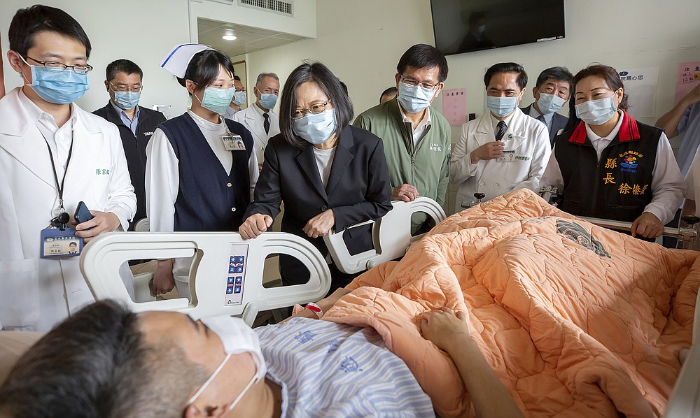 In this photo released by the Taiwan Presidential Office, Taiwan President Tsai Ing-wen visits those injured in Friday's train derailment at a near by hospital in Hualien, eastern Taiwan on Saturday, April 3, 2021. Prosecutors in Taiwan on Saturday sought an arrest warrant for the owner of an unmanned truck that rolled onto a train track and caused the country's worst rail disaster in decades, killing dozens and injuring more.(Taiwan Presidential Office via AP)