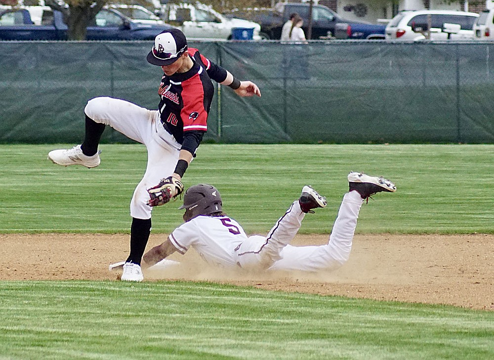 Westside Eagle Observer/RANDY MOLL Gentry's Garry Cox slides into second and almost takes down the Pea Ridge second baseman in the play on March 30 at Gentry High School. The throw missed it mark and was stopped by the centerfielder, allowing Cox to advance.