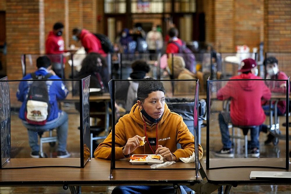 FILE - In this March 31, 2021, file photo, freshman Hugo Bautista eats lunch separated from classmates by plastic dividers at Wyandotte County High School in Kansas City, Kan., on the first day of in-person learning. With a massive infusion of federal aid coming their way, schools across the U.S. are weighing how to use the windfall to ease the harm of the pandemic — and to tackle problems that existed long before the coronavirus. (AP Photo/Charlie Riedel, File)