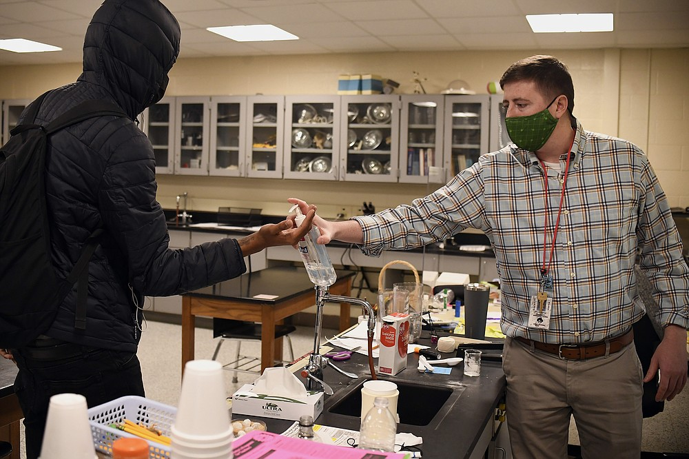 FILE - In this March 18, 2021, file photo, science teacher Christopher Duggan squirts hand sanitizer on the hands of student Jaiden Taylor, left, at Windsor Locks High School in Windsor Locks, Conn. With a massive infusion of federal aid coming their way, schools across the U.S. are weighing how to use the windfall to ease the harm of the pandemic — and to tackle problems that existed long before the coronavirus. (AP Photo/Jessica Hill, File)