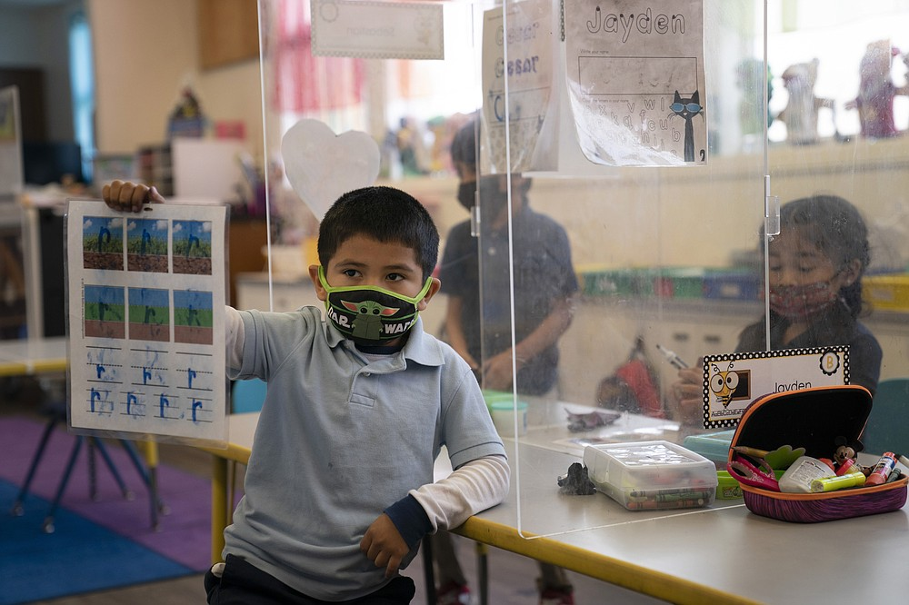 FILE - In this March 18, 2021, file photo, Cesar Verdugo, 5, shows his work to his teacher in a pre-kindergarten class at West Orange Elementary School in Orange, Calif. With a massive infusion of federal aid coming their way, schools across the U.S. are weighing how to use the windfall to ease the harm of the pandemic — and to tackle problems that existed long before the coronavirus. (AP Photo/Jae C. Hong, File)