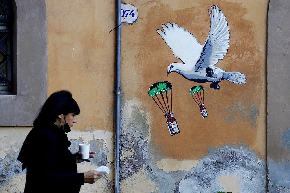A woman walks past a mural depicting a white dove parachuting COVID-19 vaccine vials, posted near the Italian Health Ministry Headquarters in Rome, Sunday, April 4, 2021. Italy has entered a three-day strict nationwide lockdown to prevent new surges of the coronavirus. Police set up road checks to ensure people were staying close to home and extra patrols were ordered up to break up large gatherings in squares and parks, which over Easter weekend are usually packed with picnic-goers. (AP Photo/Gregorio Borgia)