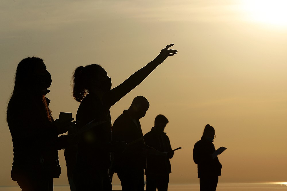 Parishioners are silhouetted against the sky as they gather and pray during an Easter sunrise service held by Park Community Church Sunday, April 4, 2021, at North Avenue Beach in Chicago. (AP Photo/Shafkat Anowar)
