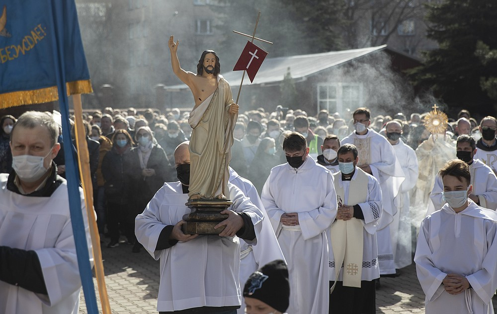 Catholic priest carries a statue of Jesus Christ as he walks in religious procession during the Holy Easter celebration in the Cathedral of the Immaculate Conception in Moscow, Russia, Sunday, April 4, 2021. (AP Photo/Pavel Golovkin)