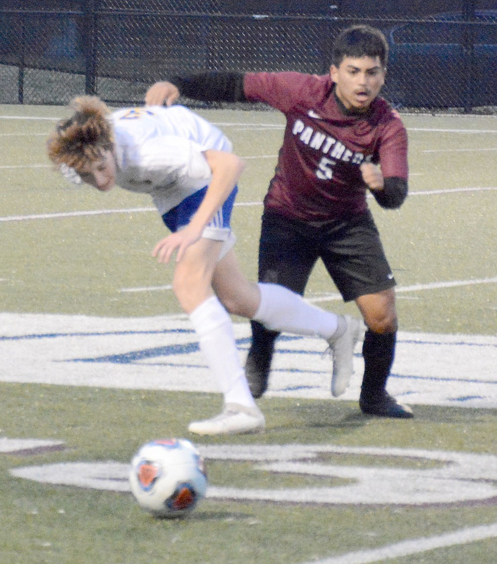 Graham Thomas/Herald-Leader Ronald Mancia battles a Mountain Home defender for the ball during a game on March 12.