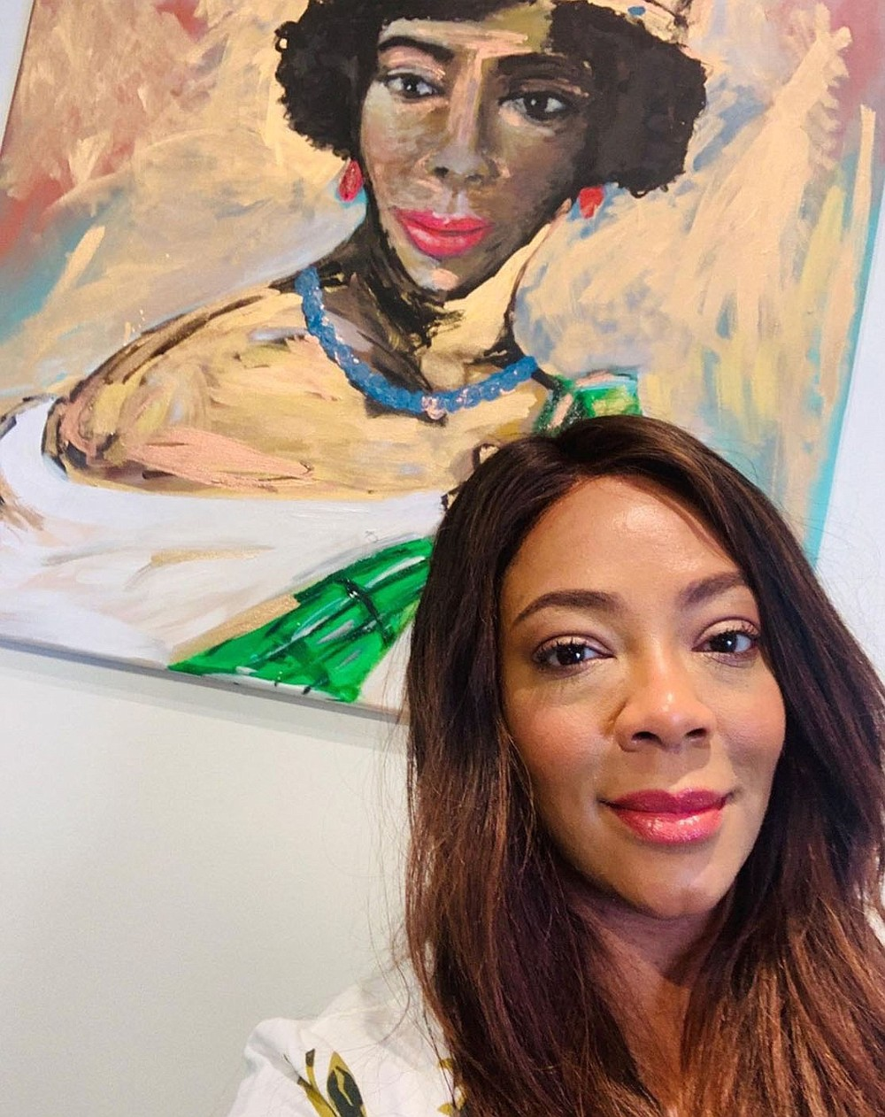 """Artist and curator Kinya Christian poses with one of her artworks on display in ìReflections of the Black Experience,"""" at the Rogers Historical Museum through Feb. 27. (Special to the Democrat-Gazette/Kinya Christian)"""