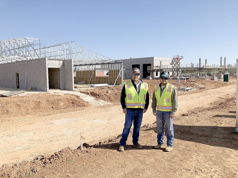 LYNN KUTTER ENTERPRISE-LEADER Doug Bryant, left, project manager, and Jonathan Parker, assistant superintendent, stand in front of the construction site for a new Prairie Grove Junior High School.