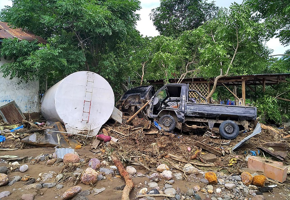 The wreckage of a pick up truck rests on a pile of flood debris in a village in Waiwerang, on Adonara Island, eastern Indonesia, Tuesday, April 6, 2021. Rescuers in remote eastern Indonesia were digging through the debris of a landslide Tuesday in search of people believed to be buried in one of several disasters brought on by severe weather in the Southeast Asian nation and neighboring East Timor. (AP Photo/Rofinus Monteiro)
