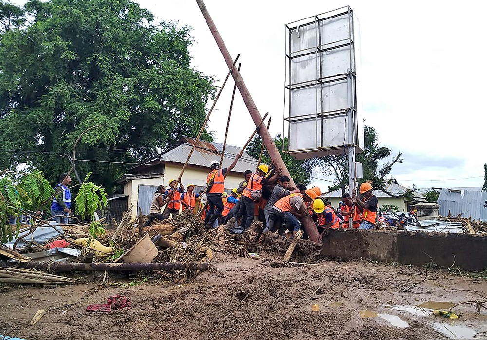 Workers raise an electricity pole to return power back to a flood affected area in Waiwerang, on Adonara Island, eastern Indonesia, Tuesday, April 6, 2021. Rescuers in remote eastern Indonesia were digging through the debris of a landslide Tuesday in search of people believed to be buried in one of several disasters brought on by severe weather in the Southeast Asian nation and neighboring East Timor. (AP Photo/Rofinus Monteiro)