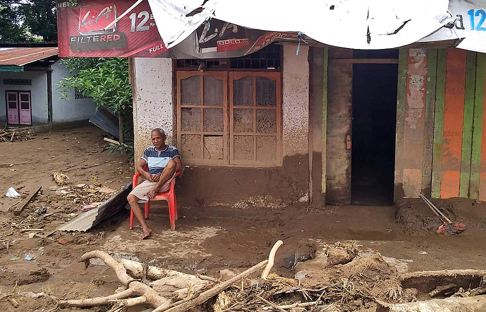 A man sits amid flood debris in front of his home in the village of Waiwerang, on Adonara Island, eastern Indonesia, Tuesday, April 6, 2021. Rescuers in remote eastern Indonesia were digging through the debris of a landslide Tuesday in search of people believed to be buried in one of several disasters brought on by severe weather in the Southeast Asian nation and neighboring East Timor. (AP Photo/Rofinus Monteiro)