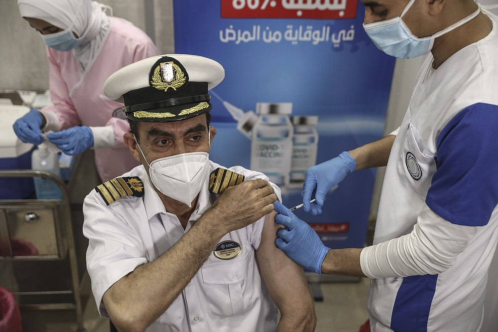 A Suec Cana pilot receives a COVID-19 vaccine in Ismailia, Egypt, Tuesday, April 6, 2021. The Suez Canal chief said Tuesday that authorities are negotiating a financial settlement with the owners of a massive vessel that blocked the crucial waterway for nearly a week. (AP Photo/Mohamed Elshahed)