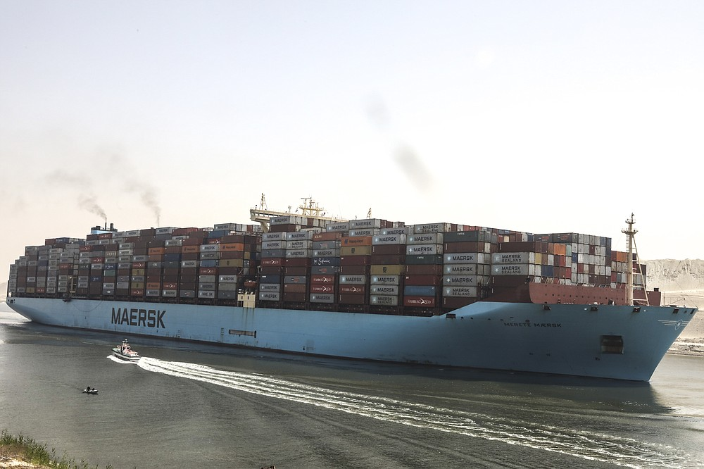 A container ship passes through Suez Canal, Egypt, Tuesday, April 6, 2021. The Suez Canal chief said that authorities are negotiating a financial settlement with the owners of a massive vessel that blocked the crucial waterway for nearly a week. (AP Photo/Mohamed Elshahed)