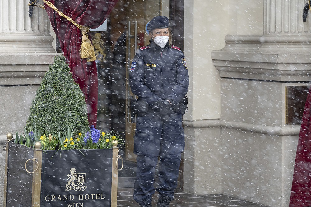 Snow falls as a police officer stands in front of the Grand Hotel Wien where closed-door nuclear talks with Iran take place in Vienna, Austria, Tuesday, April 6, 2021. Foreign ministry officials from the countries still in the accord, the so-called Joint Comprehensive Plan of Action, are meeting in Vienna to push forward efforts to bring the United States back into the 2015 deal on Iran's nuclear program. (AP Photo/Florian Schroetter)