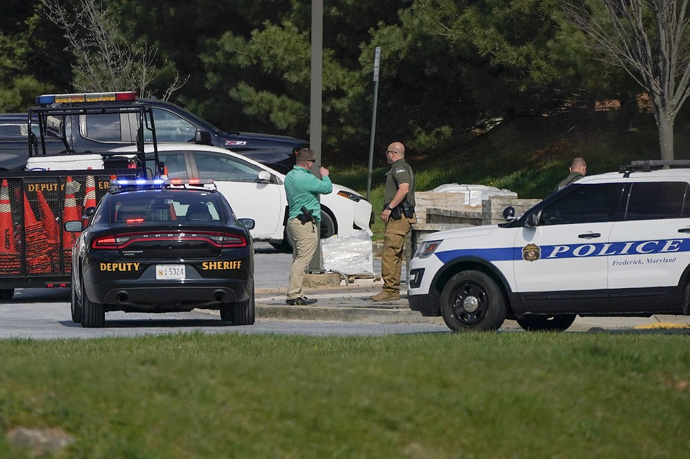 Police talk near the scene of a shooting at a business park in Frederick, Md., Tuesday, April 6, 2021. (AP Photo/Julio Cortez)