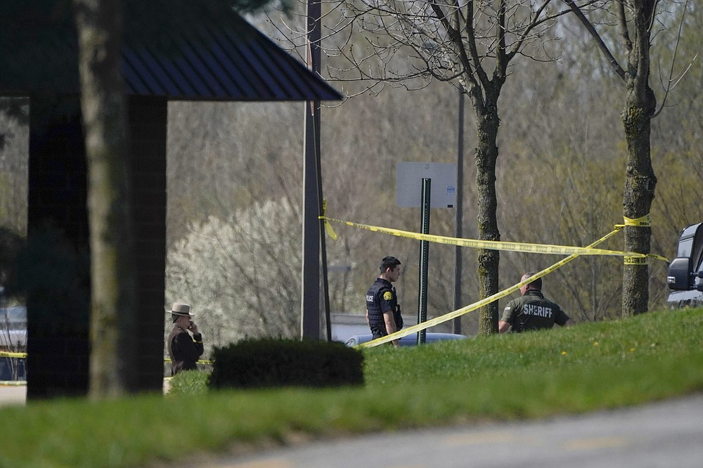 Police stand around an area cordoned off by police tape on Progress Court, near the scene of a shooting at a business park, in Frederick, Md., Tuesday, April 6, 2021. (AP Photo/Julio Cortez)