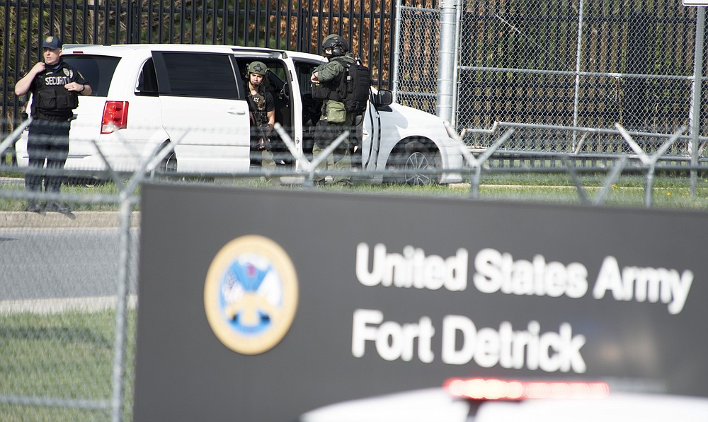 Members of the Frederick Police Department Special Response Team prepare to enter Fort Detrick at the Nallin Farm Gate in a convoy of vans and sedans, following a shooting in the Riverside Tech Park, near the Royal Farms on Monocacy Boulevard, Tuesday morning, April 6, 2021, in northeast Frederick, Md. Authorities say a Navy medic shot and critically wounded two people at a Maryland business park before fleeing to the Fort Detrick Army base, where he was shot and killed. (Graham Cullen/The Frederick News-Post via AP)