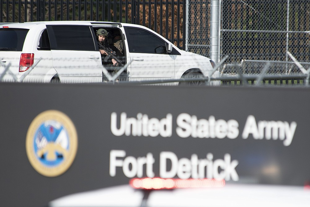 A member of the Frederick Police Department Special Response Team peers out of a minivan before the team entered Fort Detrick in a convoy of vans and sedans following a shooting in the Riverside Tech Park, near the Royal Farms on Monocacy Boulevard, Tuesday, April 6, 2021, in northeast Frederick, Md. Authorities say a Navy medic shot and critically wounded a few people at a Maryland business park before fleeing to the Fort Detrick Army base, where he was shot and killed. (Graham Cullen/The Frederick News-Post via AP)