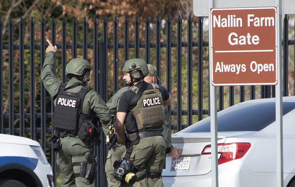 Members of the Frederick Police Department Special Response Team prepare to enter Fort Detrick at the Nallin Farm Gate in a convoy of vans and sedans following a shooting in Riverside Tech Park, near the Royal Farms on Monocacy Boulevard, Tuesday, April 6, 2021, in northeast Frederick, Md. Authorities say a Navy medic shot and critically wounded two people at a Maryland business park before fleeing to the Fort Detrick Army base, where he was shot and killed. (Graham Cullen/The Frederick News-Post via AP)