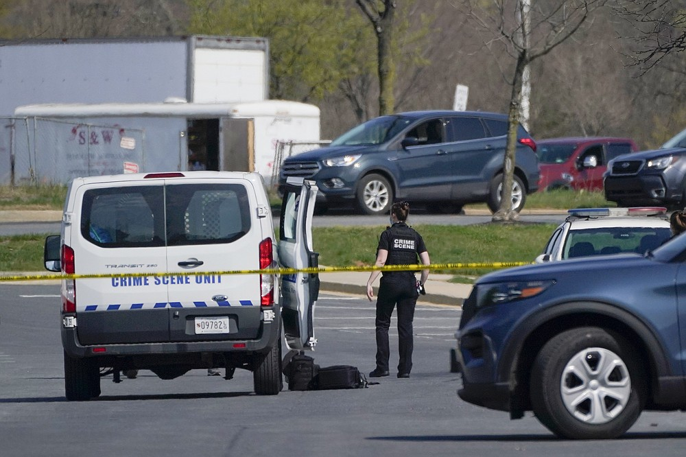 A crime scene technician stands near the scene of a shooting at a business park in Frederick, Md., Tuesday, April 6, 2021. (AP Photo/Julio Cortez)
