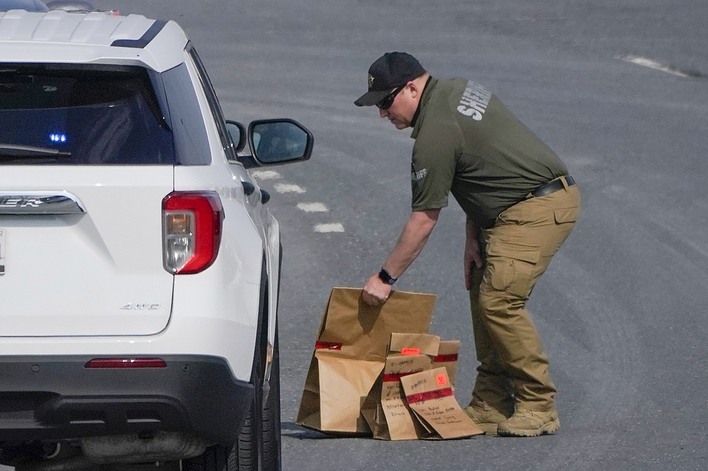 A sheriff's deputy from Frederick County, Md., puts paper bags with evidence into a police vehicle near the scene of a shooting at a business park in Frederick, Md., Tuesday, April 6, 2021. (AP Photo/Julio Cortez)
