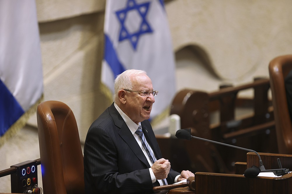 Israeli President Reuvan Rivlin speaks during the swearing-in ceremony for Israel's 24th government, at the Knesset, or parliament, in Jerusalem, Tuesday, April 6, 2021. The ceremony took place shortly after the country's president asked Prime Minister Benjamin Netanyahu to form a new majority coalition, a difficult task given the deep divisions in the fragmented parliament. (Alex Kolomoisky/Pool via AP)