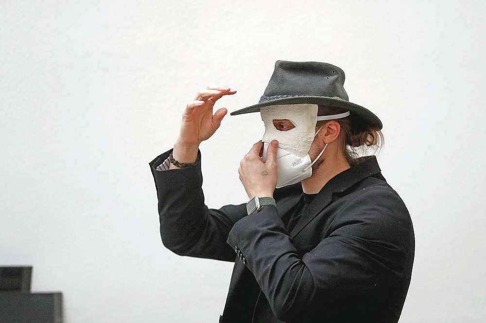 A participant adjusts his masks before taking part in an Easter procession marching through the streets in Ceske Budejovice, Czech Republic, Thursday, April 1, 2021. The traditional event went ahead despite COVID-19 restrictions, although participants also wore medical face masks and observed social distancing as a precaution. (AP Photo/Petr David Josek)