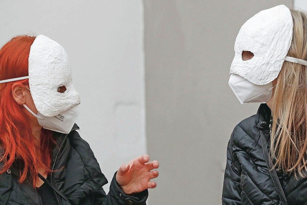 Participants talk before taking part in an Easter procession marching through the streets in Ceske Budejovice, Czech Republic, Thursday, April 1, 2021. The traditional event went ahead despite COVID-19 restrictions, although participants also wore medical face masks and observed social distancing as a precaution. (AP Photo/Petr David Josek)