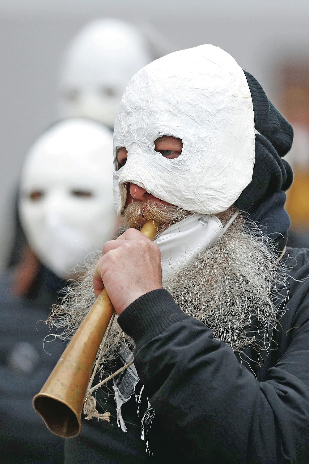 A participant blows a horn during an Easter procession marching through the streets in Ceske Budejovice, Czech Republic, Friday, April 2, 2021. (AP Photo/Petr David Josek)