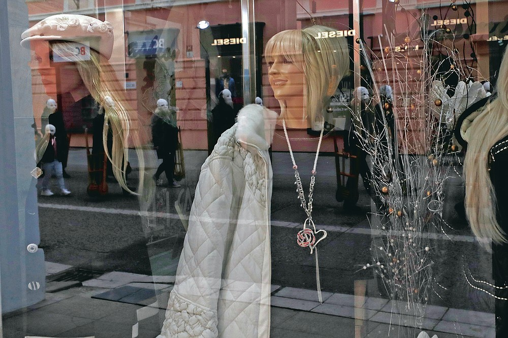 Participants dressed in black, wearing masks, beating drums and pushing small carts making a synchronized and loud sound are reflected in a shop window as they take part in an Easter procession marching through the streets of Ceske Budejovice, Czech Republic, Friday, April 2, 2021. (AP Photo/Petr David Josek)