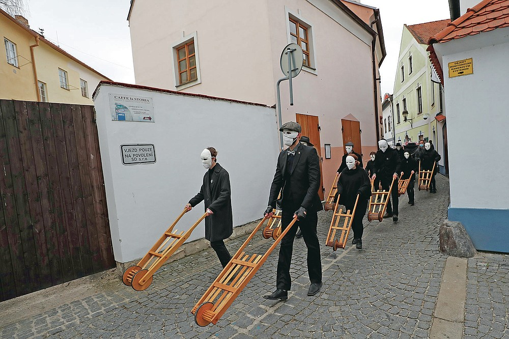 Participants dressed in black, wearing masks, beating drums and pushing small carts making a synchronized and loud sound take part in an Easter procession marching through the streets of Ceske Budejovice, Czech Republic, Friday, April 2, 2021. (AP Photo/Petr David Josek)