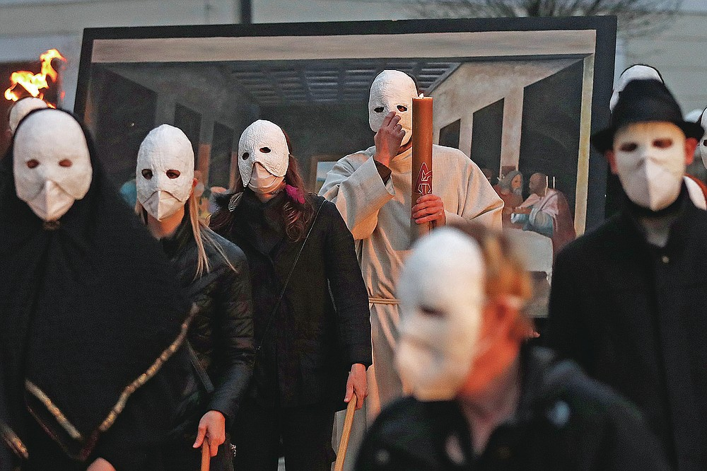 Participants dressed in black, wearing masks, beating drums and pushing small carts making a synchronized and loud sound take part in an Easter procession marching through the streets of Ceske Budejovice, Czech Republic, Thursday, April 1, 2021. (AP Photo/Petr David Josek)