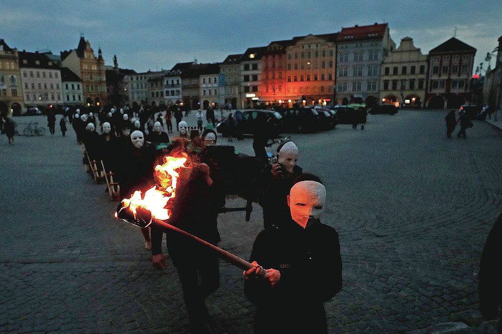 Participants dressed in black, wearing masks, beating drums and pushing small carts making a synchronized and loud sound take part in an Easter procession marching through the streets of Ceske Budejovice, Czech Republic, Thursday, April 1, 2021. The traditional event went ahead despite COVID-19 restrictions, although participants also wore medical face masks and observed social distancing as a precaution. (AP Photo/Petr David Josek)