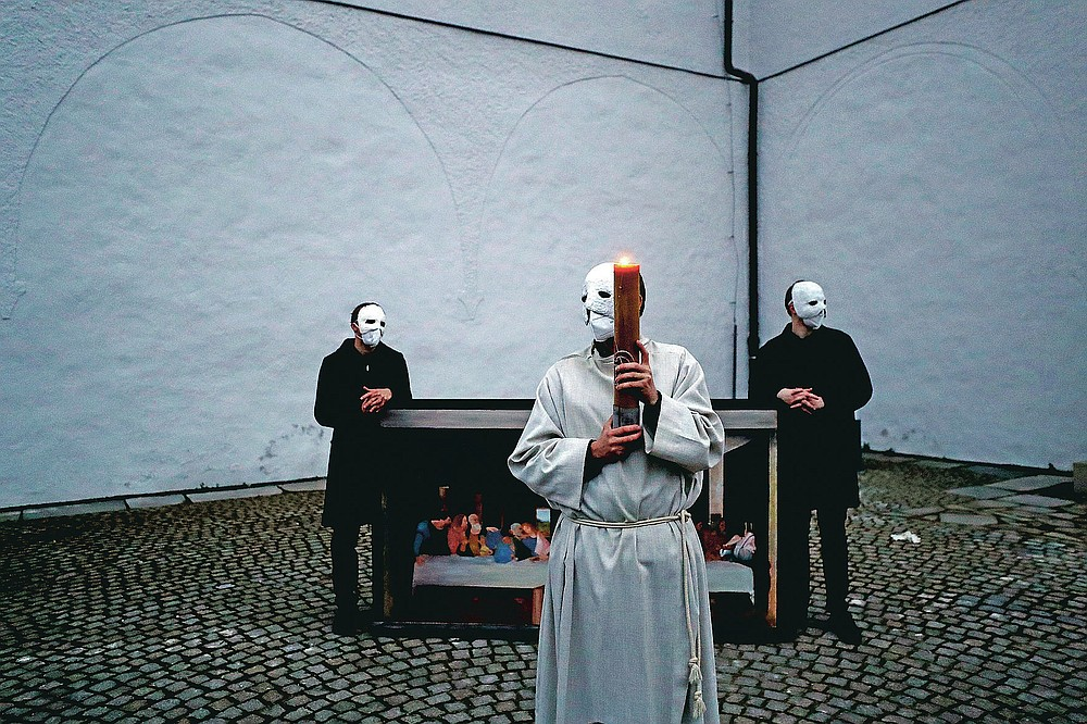 Participants wearing masks stand near a depiction of the painting the Last Supper take part in an Easter procession marching through the streets of Ceske Budejovice, Czech Republic, Thursday, April 1, 2021. (AP Photo/Petr David Josek)