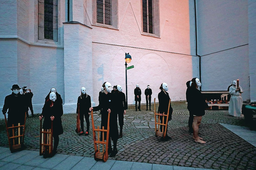 Participants wearing masks take part in an Easter procession marching through the streets of Ceske Budejovice, Czech Republic, Thursday, April 1, 2021. The traditional event went ahead despite COVID-19 restrictions, although participants also wore medical face masks and observed social distancing as a precaution. (AP Photo/Petr David Josek)
