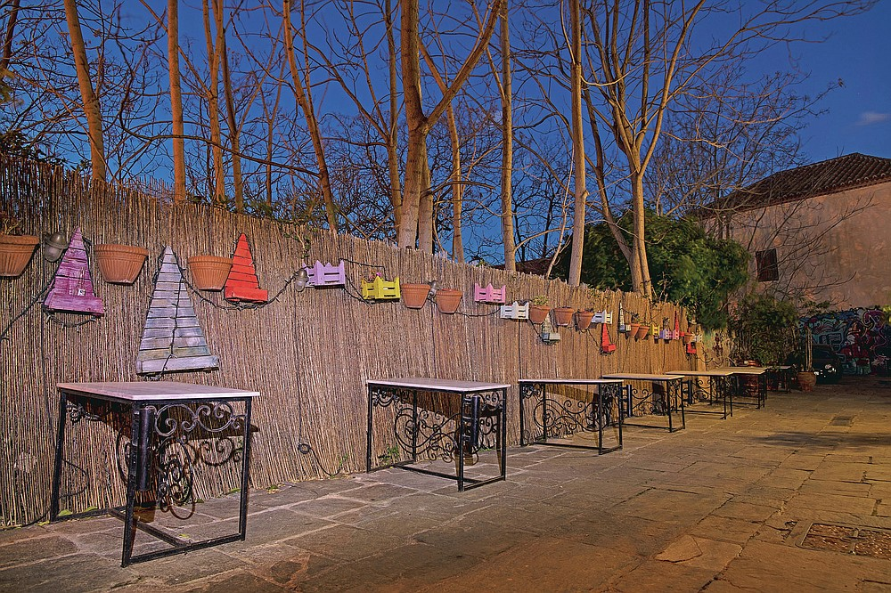 Iron tables stand in front of a decorated fence outside a shuttered traditional restaurant in Plaka, district of Athens, on Tuesday, March 16, 2021. Restaurants, bars and cafes, whose nature it is to gather groups of people closely together, have remained shut since November when the Greek government imposed a second lockdown to curb the spread of COVID-19 infections. (AP Photo/Petros Giannakouris)