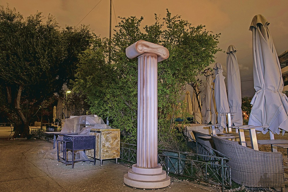A replica of an ancient Greek column stands next to stored tables and umbrellas outside a shuttered coffee shop in Thission, district of Athens, on Thursday, March 18, 2021. Restaurants, bars and cafes, whose nature it is to gather groups of people closely together, have remained shut since November when the Greek government imposed a second lockdown to curb the spread of COVID-19 infections. (AP Photo/Petros Giannakouris)