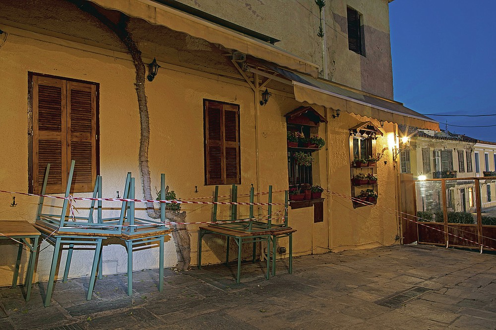 Tables are stored outside a shuttered traditional restaurant in Plaka , district of Athens, on Monday, March 29, 2021. Restaurants, bars and cafes, whose nature it is to gather groups of people closely together, have remained shut since November when the Greek government imposed a second lockdown to curb the spread of COVID-19 infections. (AP Photo/Petros Giannakouris)