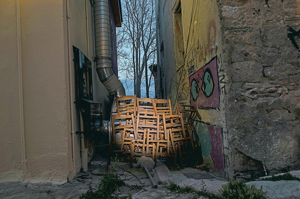 Chairs are stored outside a shuttered coffee shop in Plaka, district of Athens, on Monday, March 29, 2021. Restaurants, bars and cafes, whose nature it is to gather groups of people closely together, have remained shut since November when the Greek government imposed a second lockdown to curb the spread of COVID-19 infections. (AP Photo/Petros Giannakouris)