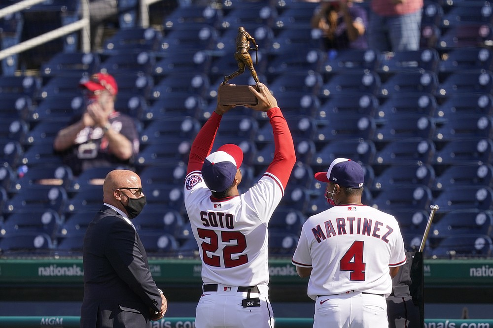Washington Nationals right fielder Juan Soto (22) holds up his 2020 National League batting title trophy alongside general manager Mike Rizzo, left, and manager Dave Martinez before an opening day baseball game against the Atlanta Braves at Nationals Park, Tuesday, April 6, 2021, in Washington. (AP Photo/Alex Brandon)