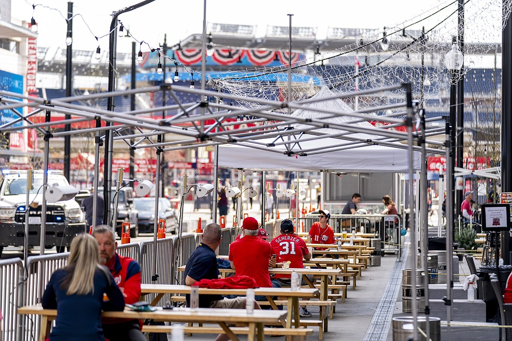 A few fans sit at outdoor bars near the centerfield gate before the Washington Nationals play the Atlanta Braves in their opening day baseball game at Nationals Park, Tuesday, April 6, 2021, in Washington. (AP Photo/Andrew Harnik)